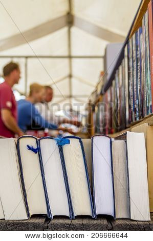Second hand hardcover books for sale in a book market people in the background