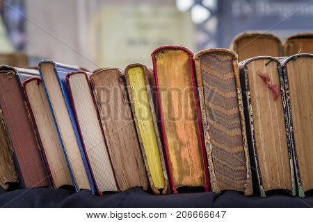 Second hand hardcover books leaning against each other for sale in a street book market