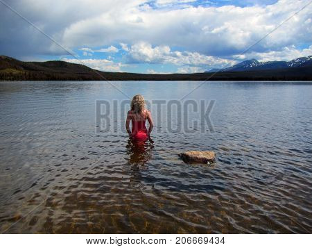 Women in a red bathing suite standing in a lake