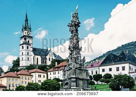 Saint Catherine's church and Plague column in Kremnica city Slovak republic. Architectural theme. Blue photo filter. Travel destination.