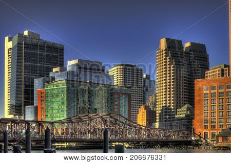 Old closed footbridge to boston seaport district and a view of the financial district buildings skyline black and white