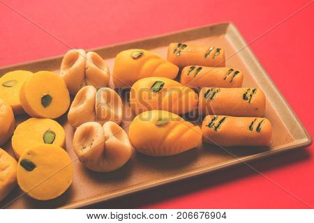 stock photo of collection of variety of sweets or orange peda or pedha or pera made up of milk, khoya, sugar , saffron etc. selective focus