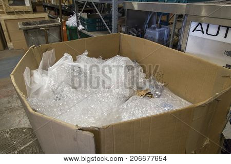 London, UK: August 18, 2017: Used bubblewrap stored in a cardboad box in an industrial unit for recycling. Shelving and industrial equipment are in the background.