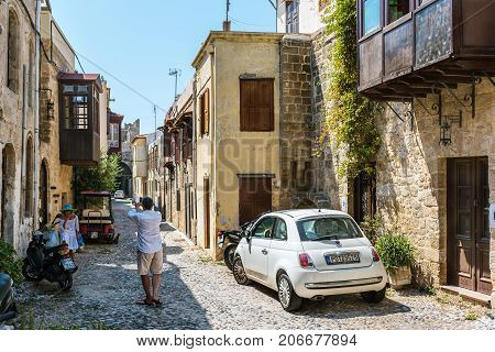 RHODES, GREECE - AUGUST 2017: Tourists are visiting street with old houses in Rhodes town on Rhodes island,  Greece
