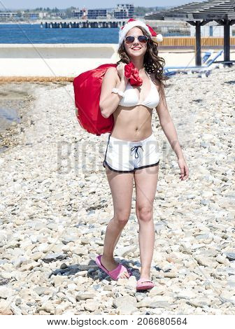 Christmas And New Year Celebration. Woman With A Bag Of Gifts Walking On Sea Beach. Girl In Swim Sui