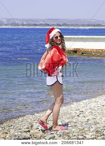 Christmas and new year celebration. Woman with a bag of gifts walking on sea beach. Girl in swim suit wearing santa costume. Winter holidays concept
