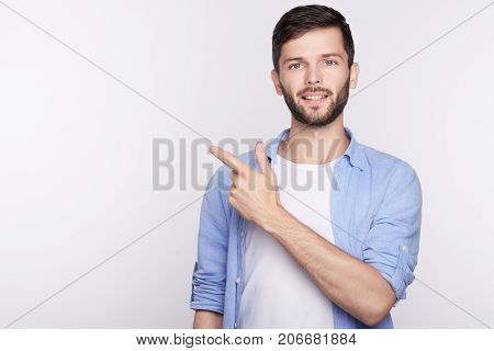 Horizontal portrait of young handsome brunette man with smile wearing casual blue shirt posing against white background pointing with index finger at white copy space for your advertisement content.