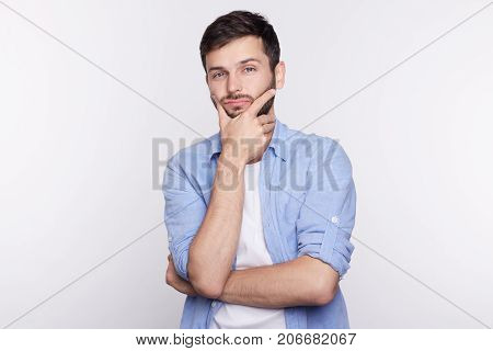 Portrait of suspicious pensive young Caucasian male in casual t-shirt touching face while thinking over something tired and trying to come up with solution having perplexed and puzzled expression.