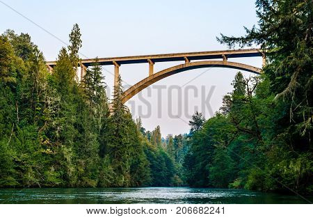 Scenic highway bridge extending over flowing river water. Nature landscape scene of beautiful forest, flowing river and bridge.