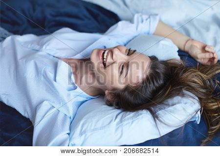 Attractive cheerful brunette female stretching in bedroom while lying in bed wearing blue shirt and jeans, laughing out loud with charming smile, full of energy, feeling excited about new happy day.