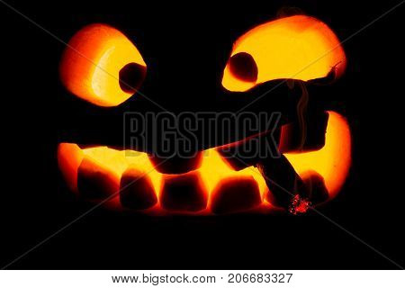 Halloween Concept. The Ghastly, Ghastly Pumpkin Glows With A Fiery Yellow Light With A Smoking Cigar