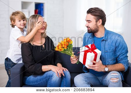 Mother's Or Female Day Concept - Little Son And Father Giving Flowers And Gift To Wife And Mother