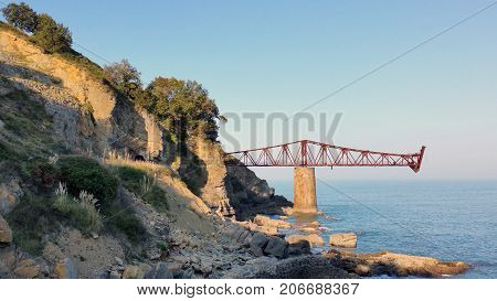Bridge To Nowhere. Abandoned Overpass For Loading Ore From An Old Mine On The Seashore. Against The