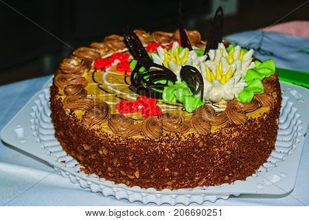Biscuit Cake With Butter Cream, Nuts And Chocolate Glaze.