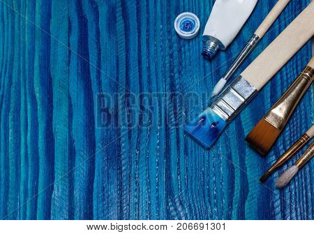 Beautiful Wooden Background Painted With Bright Blue Paint. Open A Tube Of Paint And Brushes