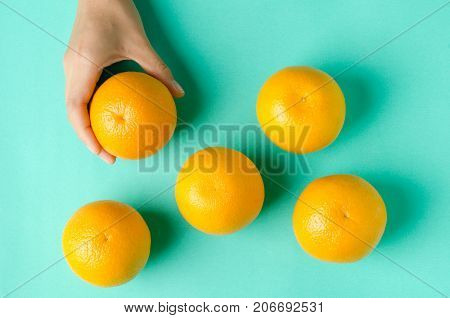 Fresh Navel oranges fruit with hand on green background.Top view of fruit