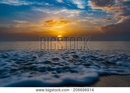 close up of moving waves with the sun rising over the ocean on a calm morning