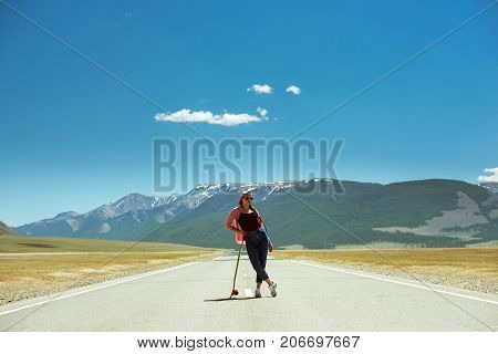 Pretty girl is posing on long straight road with with long board at mountain range. Space for text
