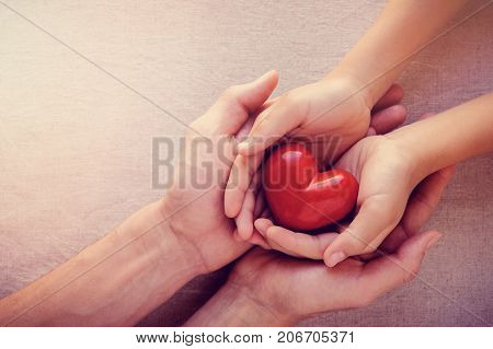 adult and child hands holiding red heart health care love give hope and family concept