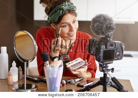 Portrait Of Happy Young Female Beauty Blogger Using Big Palette And Brush, Applying Eyeshadow While