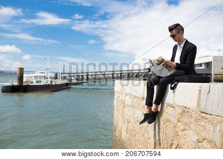 Busy modern student resting with newspaper on dock and reading interesting article while sitting on edge of concrete slab. Mass media concept