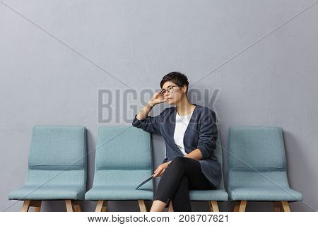 Sad Upset Female Job Seeker Being Thick And Tired Of Finding Work, Sits On Chair Before Talk With Em