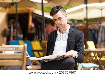 Concentrated stylish man following actual news reading newspaper in sidewalk cafe and enjoying summer weather. Morning of businessman concept