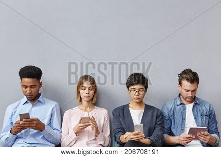 Horizontal Portrait Of Four Job Applicants Wait In Waiting Room, Being Addicted From Modern Gadgets,