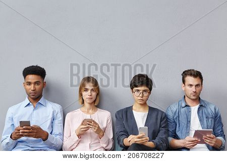 Half Length Portait Of Four Interracial People Or Ambitious Job Seekers Hold Modern Gadgets In Hands