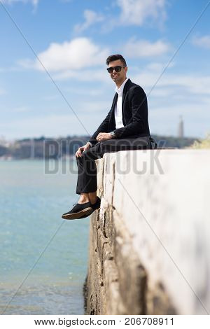 Smiling handsome fashionable man resting on dock and looking at camera. Positive young student resting after classes. Happy guy enjoying stroll. Businessman concept