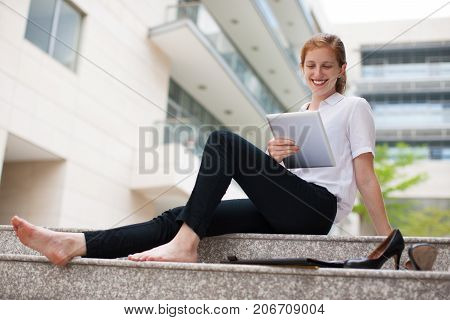 Portrait of cheerful barefoot young Caucasian businesswoman or student sitting on staircase using touchpad and smiling. Work life balance concept