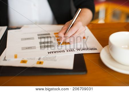 Close-up of female hand making notes in paperwork at table in cafe. Work life balance concept