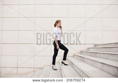Happy young Caucasian businesswoman walking upstairs, calling up and smiling. Business and communication concept