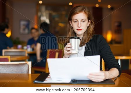 Portrait of serious young Caucasian businesswoman sitting at table, reading document and drinking coffee at cafe. Work life balance concept