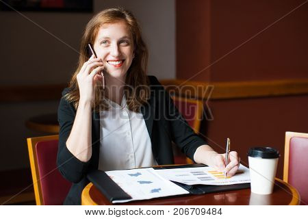 Portrait of smiling young Caucasian businesswoman sitting at table, working with papers and talking on mobile phone in cafe. Work life balance concept