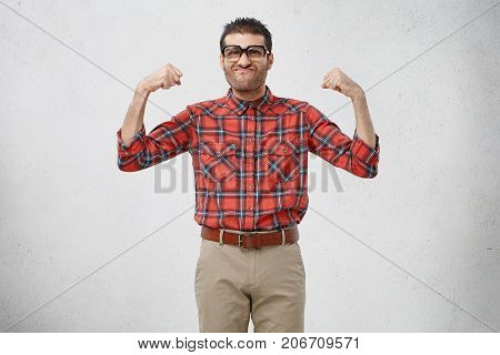 Funny Ridiculous Bearded Guy Wearing Eyeglasses With Thick Lenses And Checkered Red Shirt Posing In