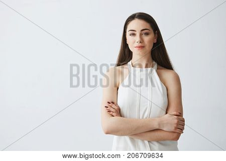 Portrait of young beautiful businesswoman looking at camera with crossed arms over white background. Copy space.