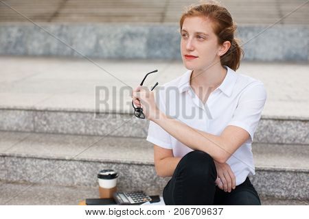 Portrait of thoughtful young Caucasian businesswoman holding glasses sitting on staircase. Work life balance concept