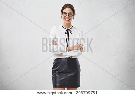 Glad Smiling Female Teacher Wears Elegant Clothes And Spectacles, Being Happy To Hear Thankful Words
