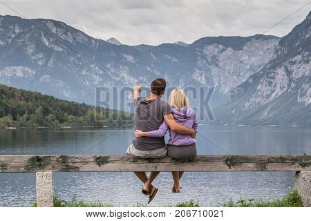 Embraced casual couple watching tranquil overcast morning scene at lake Bohinj, Alps mountains, Slovenia. poster