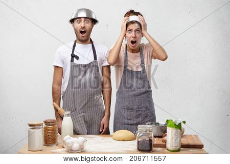 Young Female Cook Being In Panic, Keeps Hand On Head, Looks Desperately And With Jaw Dropped, Has Pr