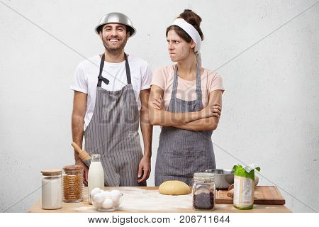 Angry Gloomy Female Looks At Opponent, Being Irritated That He Won Culinary Competition, Keeps Hand