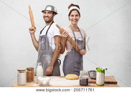 Smiling Male And Female Competitors Stand Back To Each Other, Hold Rolling Pins, Take Part In Culina