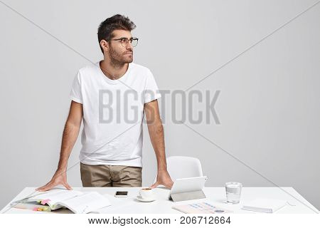 Horizontal Portrait Of Bearded Businessman Wears Casual Clothes And Glasses, Stands At Office Desk,