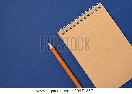 Top view of open spiral blank notebook with pencil on blue paper background. Open vintage notebook. Empty notebook paper for text with  pencil . office concept top view.Copy space. Space for text.
