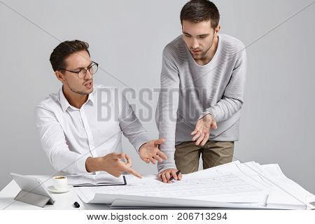 Two Male Colleagues Architects Having Argument Concerning Architectural Plan, Expressing Their Point