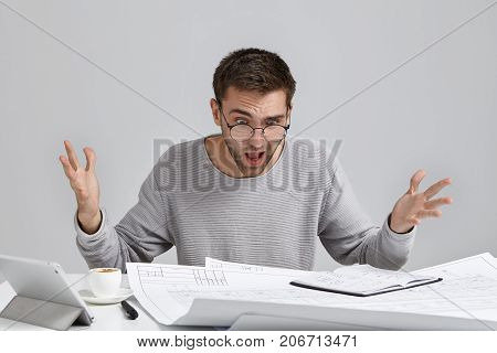 Young Puzzled Young Architect Feels Indignant, Looks Ar Drawings On Table, Realizes That He Made Mis