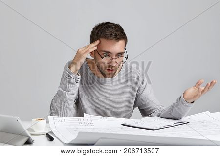 Portrait Of Confused Male Designer Or Architect, Feels Stressed, Being Nervous, Keeps Hand On Head,