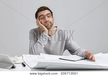 People, Job, Tiresome And Overwork Concept. Bored Sleepy Male Engineer Working On Blueprints Late At