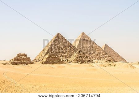 Giza pyramids in Cairo, Egypt. General view of pyramids from the Giza Plateau Three pyramids known as Queens' Pyramids on front side. Next in order from left, the Pyramid of Menkaure, Khafre and Chufu